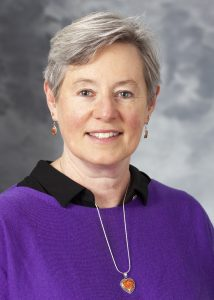 A headshot of a woman with grey hair. She is wearing a black shirt and purple sweater and is smiling at the camera.