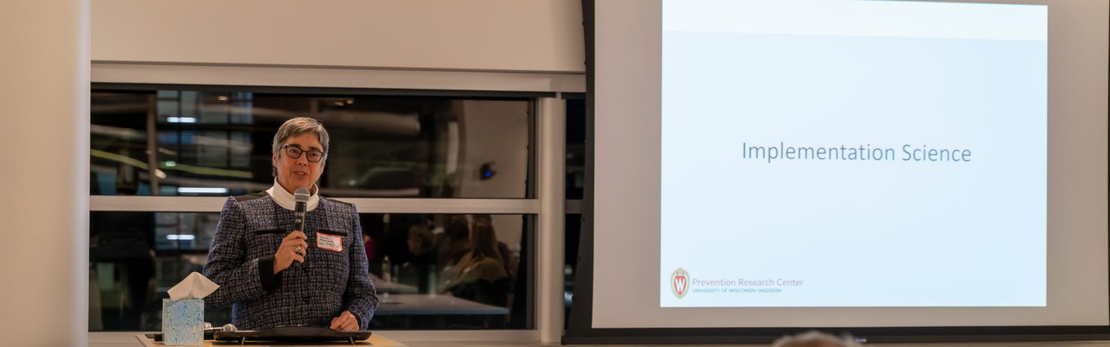 A photo of a woman standing and speaking at a podium in front of a presentation screen.