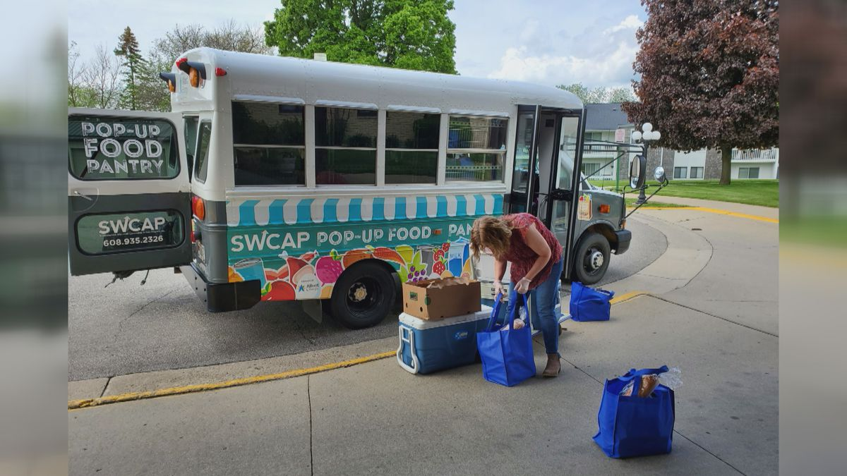 Image of a person unloading groceries from a colorfully decorated bus
