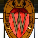 The UW crest in stained glass on a window.